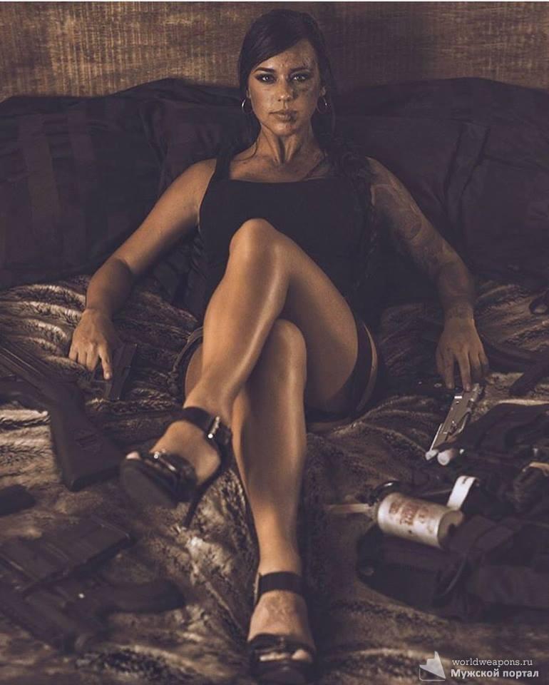 Красивая девушка с оружием, в черном платье, брутально, на кровати.