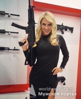 Модель с оружейного шоу. Красивая девушка с оружием. Блондинка в черном платье.