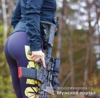 Красивая, спортивная девушка с оружием, в лосинах. Попа.