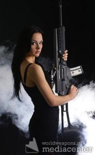 Сексуальная девушка с оружием, в дыму. Sexy woman with weapon on smoky background.