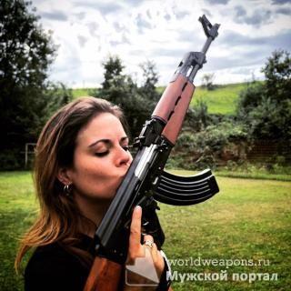Красивая девушка с оружием, целует автомат Калашникова.